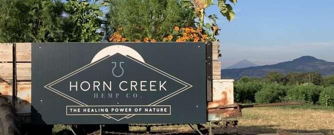 horn creek hemp logo sign on trailer in hemp fields